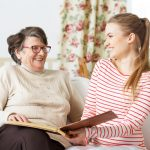Home care aide and senior woman with scrap book